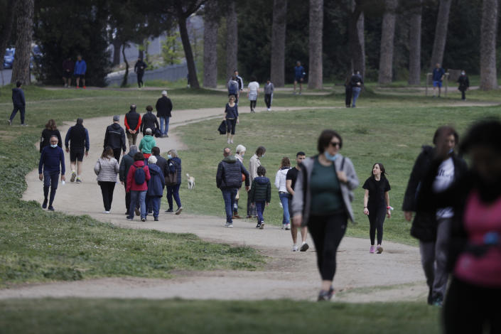 People stroll at Rome's Villa Pamphili park, Monday, April 5, 2021. Italy has entered a three-day strict nationwide lockdown to prevent new surges of the coronavirus. Police set up road checks to ensure people were staying close to home and extra patrols were ordered up to break up large gatherings in squares and parks, which over Easter weekend are usually packed with picnic-goers. (AP Photo/Gregorio Borgia)