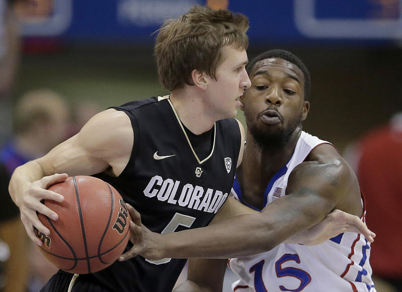 Kansas guard Elijah Johnson (15) tries to steal the ball away from Colorado guard Eli Stalzer (5) during the first half of an NCAA college basketball game Saturday, Dec. 8, 2012, in Lawrence, Kan. (AP Photo/Charlie Riedel)