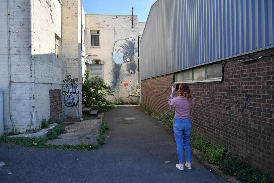 A woman photographs Banksy's Girl with a Pierced Eardrum mural, who has been given a face mask in a nod to the coronavirus pandemic, at Hanover Place in Bristol, as the UK continues in lockdown to help curb the spread of the coronavirus.