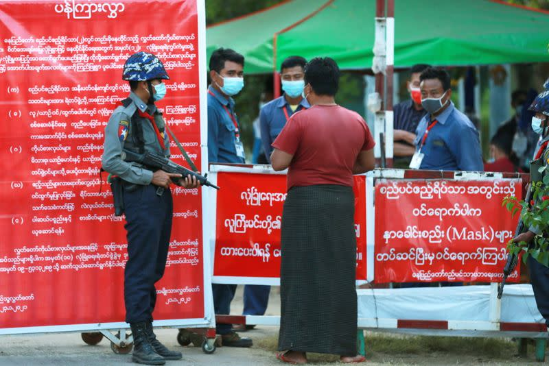 Myanmar's police officers stand guard at the entrance of parliament members residence at the congress compound in Naypyitaw