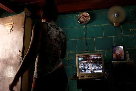 A woman walks past a TV showing the broadcast of the National Assembly session, in Havana, Cuba July 21, 2018. REUTERS/ Stringer