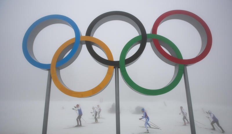 Cross-country skiers train underneath the olympic rings at the Laura biathlon and cross-country ski center, at the 2014 Winter Olympics, Monday, Feb. 17, 2014, in Krasnaya Polyana, Russia. After days of warm weather at the Sochi Olympics, fog up in the mountains is causing an even bigger disturbance. Thick fog rolled in over the mountains in Krasnaya Polyana on Sunday night and was still lingering on Monday, and the limited visibility forced organizers to delay a biathlon race and cancel the seeding runs in a snowboard event. (AP Photo/Gero Breloer)