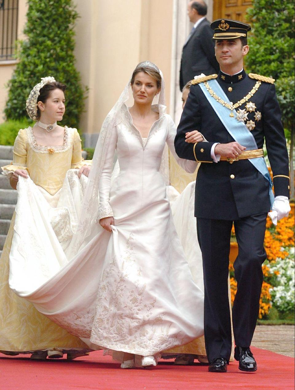 "<p>The always chic Queen Letizia walked down the aisle in a collared <span class=""redactor-unlink"">Manuel Pertegaz</span> gown that featured a stunning train.</p>"