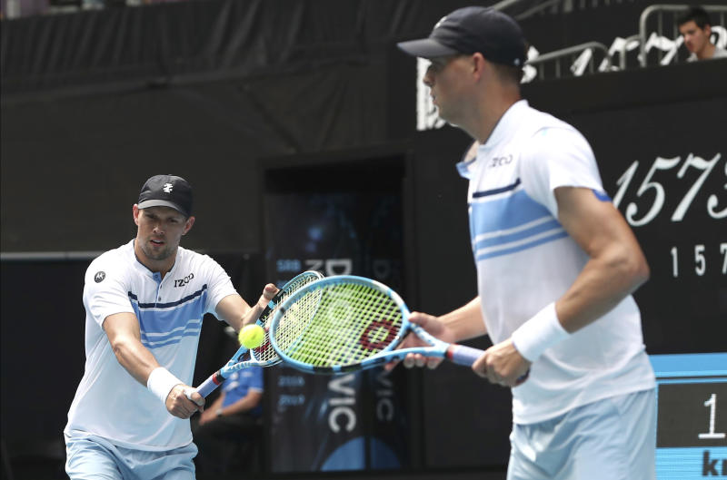 Mike Bryan, left, of the U.S. makes a backhand return as his brother Bob watches during their third round doubles match against Croatia's Ivan Dodig and Slovakia's Filip Polasek at the Australian Open tennis championship in Melbourne, Australia, Monday, Jan. 27, 2020. (AP Photo/Dita Alangkara)