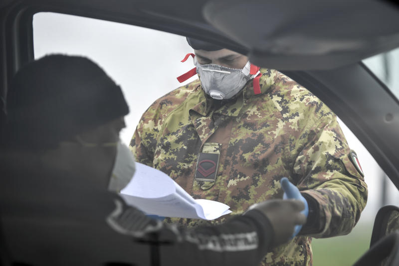 An Italian Army soldier checks transit to and from the cordoned areas near Turano Lodigiano, Northern Italy, Tuesday, Feb. 25, 2020. Civil protection officials on Tuesday reported a large jump of cases in Italy, from 222 to 283. Seven people have died, all of them elderly people suffering other pathologies. (Claudio Furlan/Lapresse via AP)