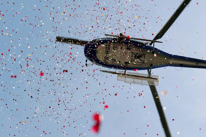 A helicopter showers flowers in honor of victims of the collapse of a dam owned by Brazilian mining company Vale SA, in Brumadinho, Brazil February 25, 2019.