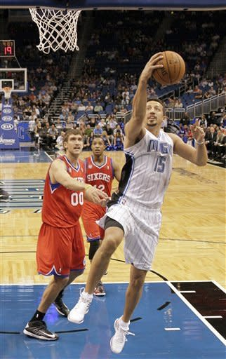 Orlando Magic's Hedo Turkoglu (15), of Turkey, gets off a shot in front of Philadelphia 76ers' Spencer Hawes (00) and Evan Turner during the first half of an NBA preseason basketball game, Thursday, Oct. 11, 2012, in Orlando, Fla. (AP Photo/John Raoux)