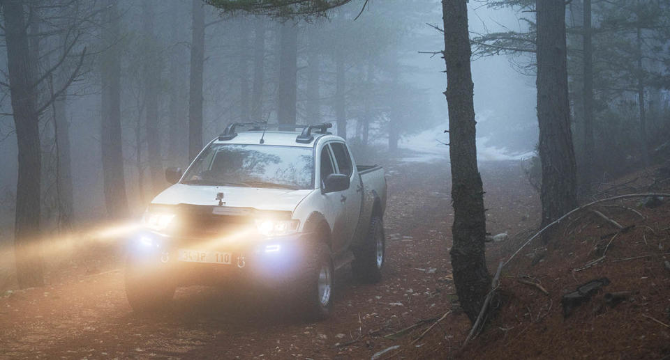A car drives through woods with headlights and fog lights on. Source: Getty Images