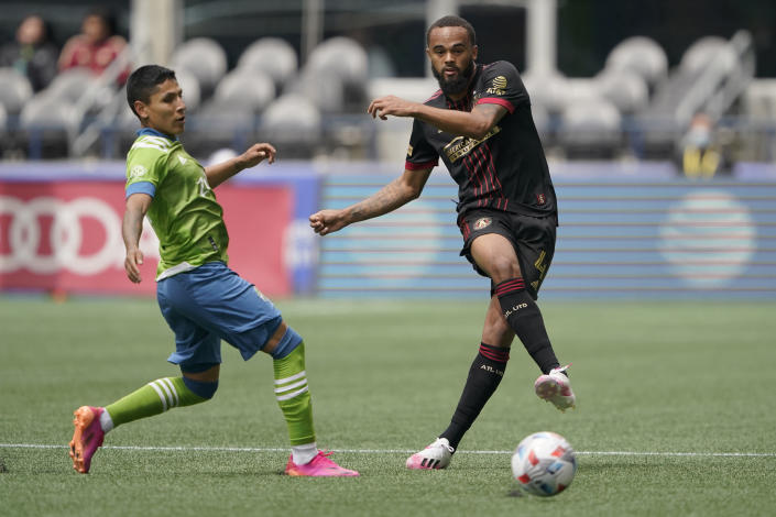 Atlanta United defender Anton Walkes, right, kicks the ball in front of Seattle Sounders forward Raul Ruidiaz, left, during the first half of an MLS soccer match, Sunday, May 23, 2021, in Seattle. (AP Photo/Ted S. Warren)