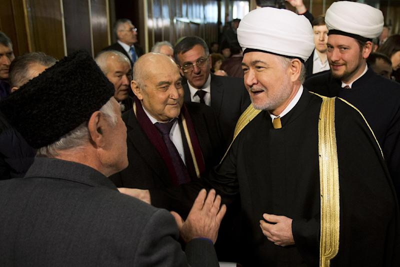 Crimean Tatars greet Russia's top Muslim Cleric Ravil Gainutdin, foreground right, during the Crimean Tatar Qurultay, a religious congress, in Bakhchysarai, Crimea, Saturday, March 29, 2014. The Crimean Tatar Qurultay, a religious congress will determine whether the Tatars will accept Russian citizenship and the political system that comes with it, or remain Ukrainian citizens on Russian soil. (AP Photo/Pavel Golovkin)