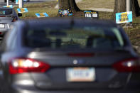 Motorists drive past yard signs in an Indianapolis neighborhood advertising the NCAA college basketball tournament Friday, March 19, 2021. (AP Photo/Charles Rex Arbogast)