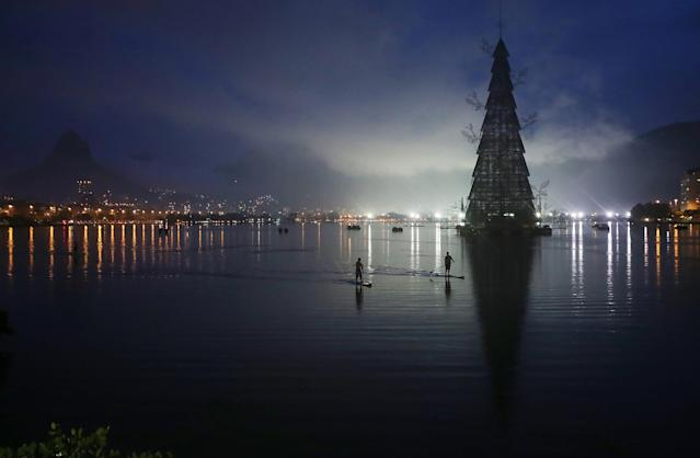 RIO DE JANEIRO, BRAZIL - NOVEMBER 30: Stand-up paddle boarders row past before the lighting ceremony for Rio de Janeiro's famed floating Christmas tree in Lagoa Rodrigo de Freitas on November 30, 2013 in Rio de Janeiro, Brazil. The lagoon will be used as a venue for rowing events during the Rio 2016 Olympic Games. The constructed tree is the largest floating Christmas tree in the world according to the Guinness Book of World Records. The tree is 85 meters tall and is displayed by three million microlights. (Photo by Mario Tama/Getty Images)