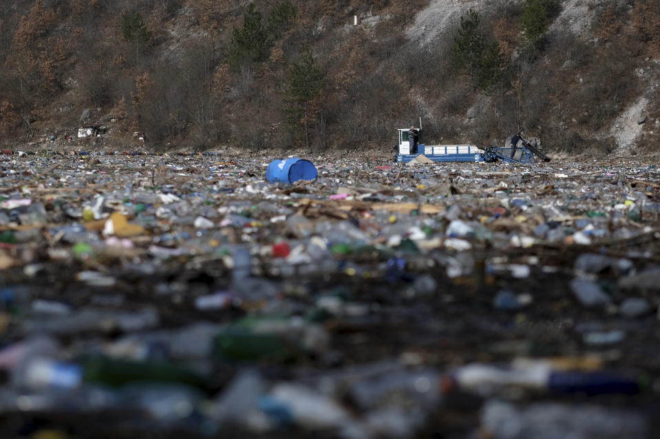 A machine collects garbage from the Drina river near Visegrad, eastern Bosnia, Wednesday, Feb. 24, 2021. Environmental activists in Bosnia are warning that tons of garbage floating down the Balkan country's rivers are endangering the local ecosystem and people's health. The Drina River has been covered for weeks with trash that has piled up faster than the authorities can clear it out. (AP Photo/Kemal Softic)