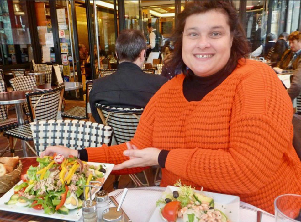 A photo of Sydney woman Maria wearing an orange jumper at a restaurant