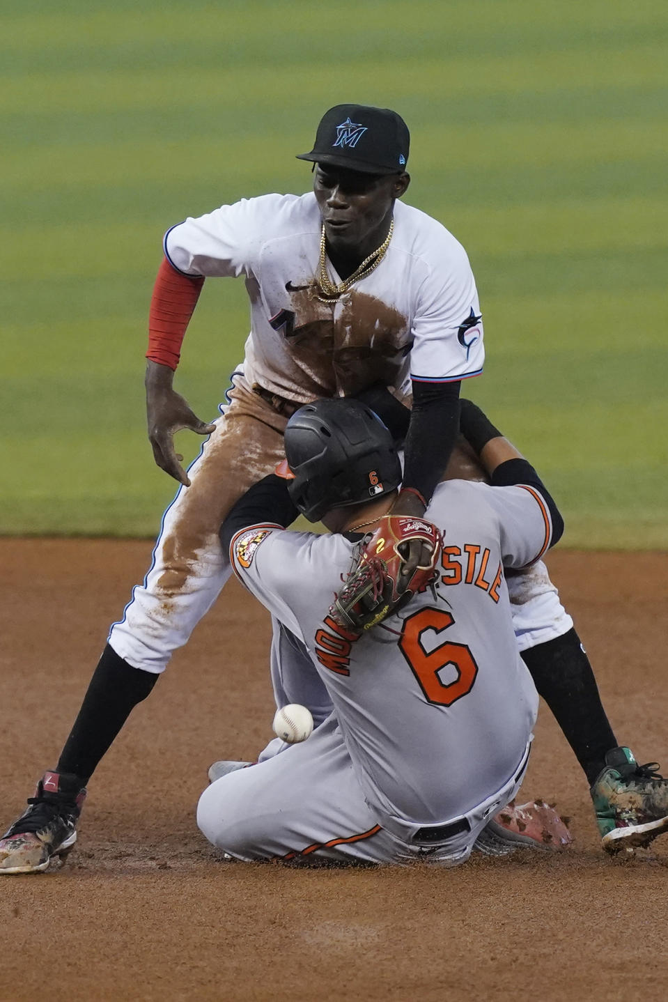 Miami Marlins second baseman Jazz Chisholm Jr., rear, drops the ball as Baltimore Orioles' Ryan Mountcastle (6) steals the base during the third inning of a baseball game, Wednesday, April 21, 2021, in Miami. (AP Photo/Marta Lavandier)