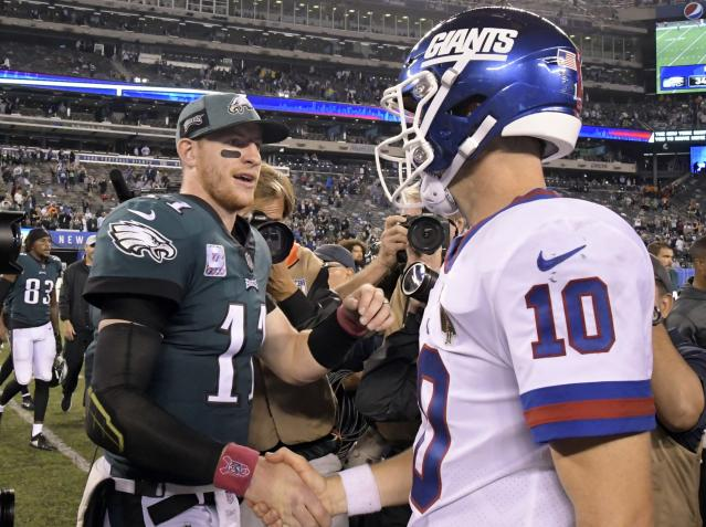 Philadelphia Eagles quarterback Carson Wentz (11) shakes hands with New York Giants quarterback Eli Manning (10) after an NFL football game Thursday, Oct. 11, 2018, in East Rutherford, N.J. The Eagles won 34-13. (AP Photo/Bill Kostroun)