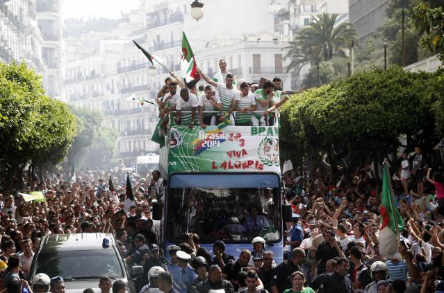 Algeria's soccer players (on bus) are welcomed by fans in downtown Algiers, after returning from the 2014 World Cup soccer tournament, July 2, 2014. Algeria was knocked out from the World Cup by Germany after reaching the round of 16 for the first time. REUTERS/Ramzi Boudina (ALGERIA Tags: - Tags: SPORT SOCCER WORLD CUP)