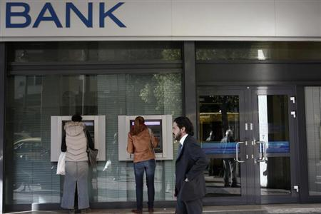 People make transactions at ATMs of an Alpha bank branch in Athens