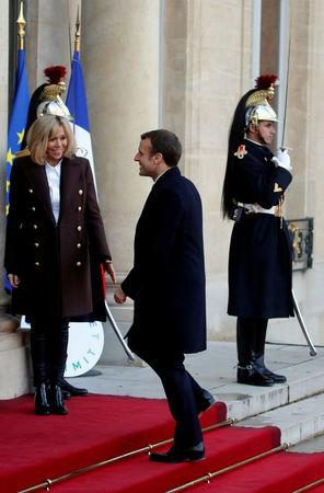 FILE PHOTO: French President Emmanuel Macron and his wife Brigitte Macron welcome guests for a lunch at the Elysee Palace as part of the One Planet Summit in Paris, France, December 12, 2017. REUTERS/Philippe Wojazer/File Photo