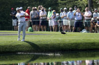 Patrons watches as Bryson DeChambeau skip his ball across the pond to the 16th green during a practice round for the Masters golf tournament at Augusta National Golf Club on Wednesday, April 7, 2021, in Augusta, Ga. (Curtis Compton/Atlanta Journal-Constitution via AP)