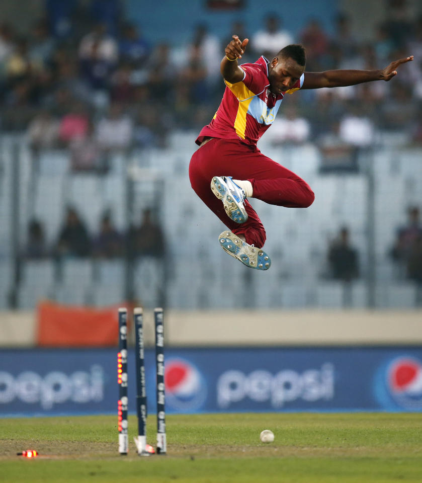 West Indies' bowler Andre Russell leaps in the air to celebrate the dismissal of Sri Lanka's batsman Seekkuge Prasanna during their ICC Twenty20 Cricket World Cup warm up match in Dhaka, Bangladesh, Wednesday, March 19, 2014. (AP Photo/Aijaz Rahi)