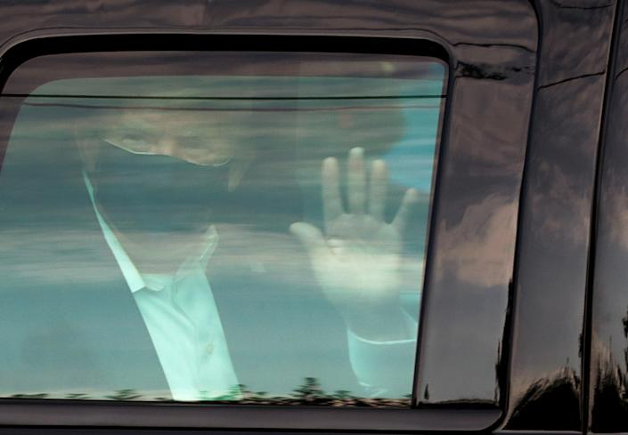 President Trump waves to supporters in front of Walter Reed National Military Medical Center in Bethesda, Md., on Sunday. (Cheriss May/Reuters)