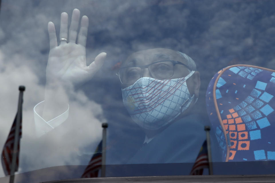 Former Deputy Prime Minister Ismail Sabri Yaakob waves to media as he departs for the national palace, at UMNO Headquarters in Kuala Lumpur, Malaysia, Thursday, Aug. 19, 2021. Former Deputy Prime Minister Ismail appeared to have won majority support to be Malaysia's new leader. His backers have been summoned to the palace Thursday to verify to the king they support him. (AP Photo/FL Wong)