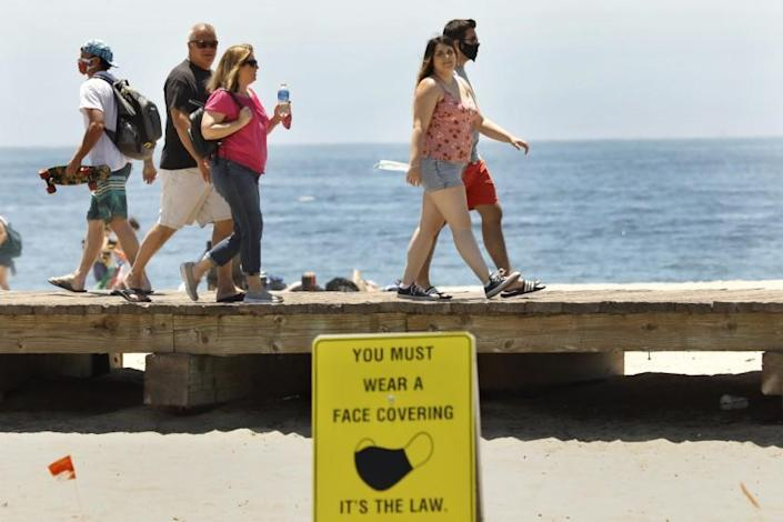 "In Laguna Beach, California, signs are posted that read ""You must wear a face covering. It's the law,"" but not everyone is doing it. <span class=""copyright"">(Carolyn Cole / Los Angeles Times)</span>"