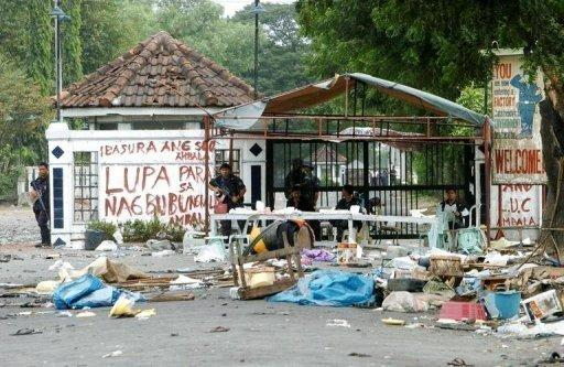 Armed Philippines police guard the entrance to the Hacienda Luisita farm after seven people were killed in deadly riots in 2004. Manila's land reform agency said it was ready to carve up the vast farm of President Benigno Aquino's clan, which lost a Supreme Court battle for $USD100 million in compensation