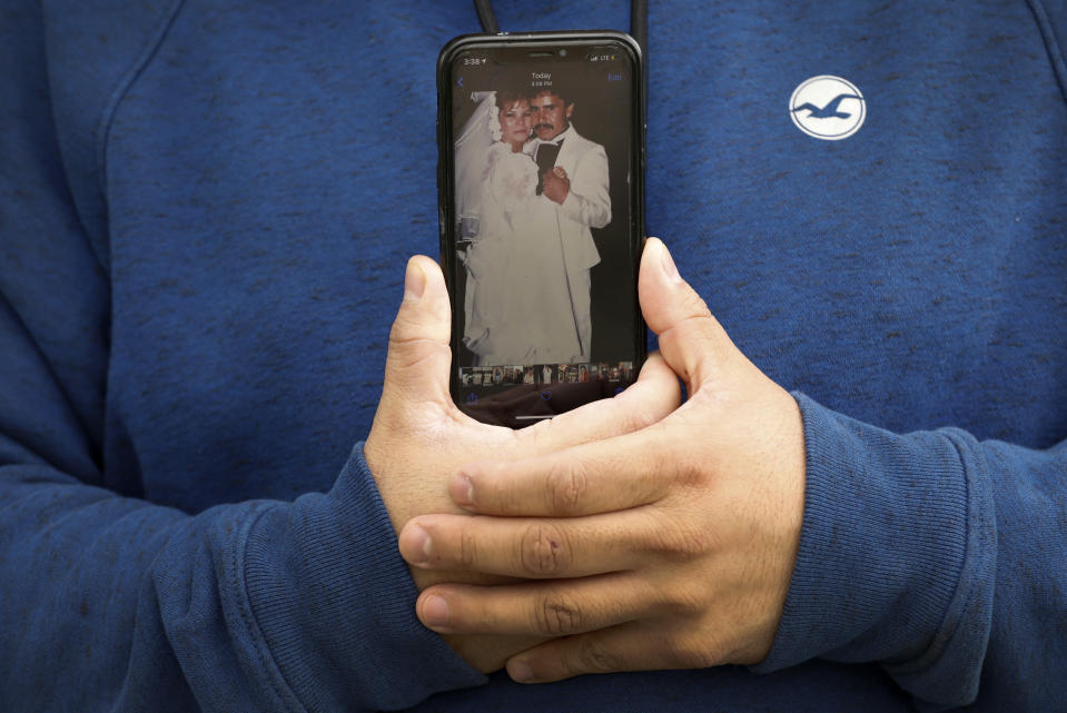 Omar Martinez holds his cell phone displaying a photo from his parents' wedding, Saturday, April 25, 2020, in West Liberty, Iowa. Martinez's family had been living the American dream after immigrating from Mexico in the 1990s and settling in this small town in eastern Iowa, but their lives fell apart after coronavirus infections spread from his mother to his sister and his father. Now he is planning his father's funeral while hoping his sister recovers in a hospital intensive care unit. He is grateful his mother is better and appreciates the community's support. (AP Photo/Charlie Neibergall)