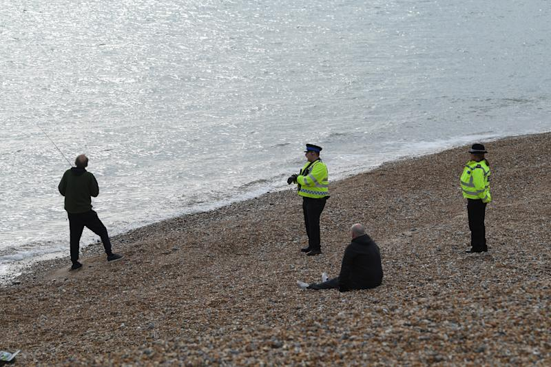BRIGHTON, ENGLAND - APRIL 01: Police community support officers patrolling Brighton beach talk to a member of the public fishing on April 01, 2020 in Brighton, England. The Coronavirus (COVID-19) pandemic has spread to many countries across the world, claiming over 40,000 lives and infecting hundreds of thousands more. (Photo by Mike Hewitt/Getty Images)