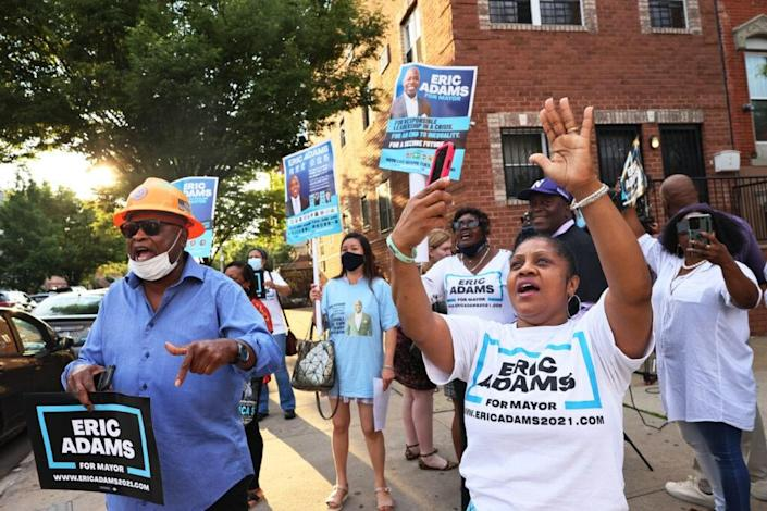 Supporters of New York City mayoral candidate Eric Adams celebrate after he exits his polling location after voting during Primary Election Day at P.S. 81 on June 22, 2021 in the Bedford-Stuyvesant neighborhood of Brooklyn borough in New York City. (Photo by Michael M. Santiago/Getty Images)