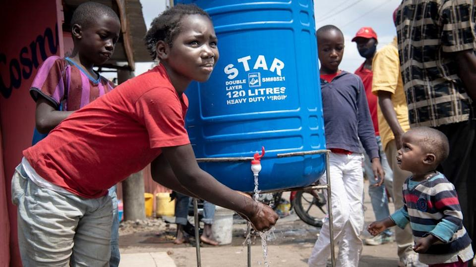 Kids in Mathare help each other to wash hands at a hand washing station on July 6, 2020 in Nairobi, Kenya