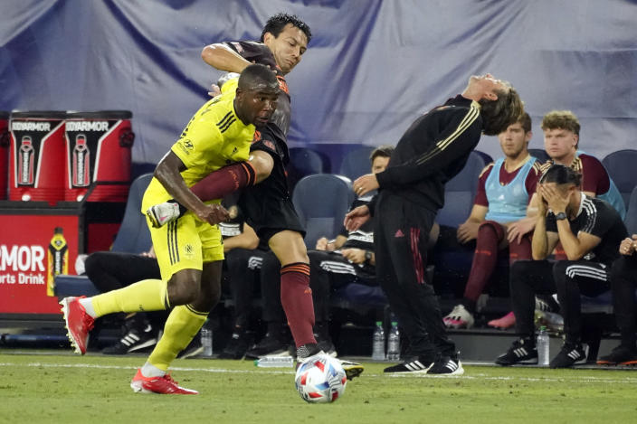 Atlanta United coach Gabriel Heinze, right, reacts to a play as Nashville SC defender Nick Hinds, left, and Atlanta defender George Bello (21) vie for the ball during the first half of an MLS soccer match Thursday, July 8, 2021, in Nashville, Tenn. (AP Photo/Mark Humphrey)