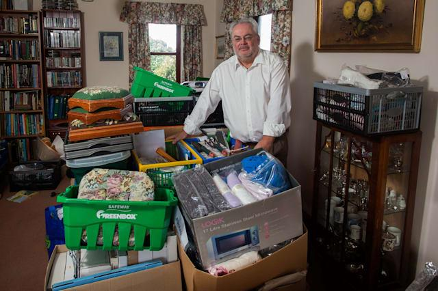 Chris Rae, from St Buryan, Cornwall, with some of the  items his father has brought through postal scams. His father Samuel has severe dementia and he has lost �35,000 because of the scams. 01/09/2015 See SWNS story SWSCAM; A retired Army colonel and dementia sufferer was targeted by fraudsters who conned him out of �35,000 � after he failed to tick one box when filling out a survey. Samuel Rae, 87, was targeted by the fraudsters after he filled out a survey for a charity he supported, but failed to tick a box stating that he did not want his details shared. He was contacted over 700 times by 12 different firms, some of which tried to convince him he has won vast sums of money in prizes. In total Mr Rae was conned out of �35,000, and the scam only came to an end when his son, Chris Rae, visited him to find his home filled with hundreds of scam letters.