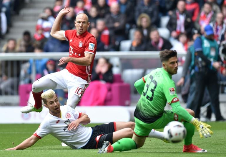 Bayern Munich's Arjen Robben (2ndL) scores the first goal for Munich against Mainz's goalkeeper Jannik Huth (R) during their German First division Bundesliga football match in Munich, Germany, on April 22, 2017