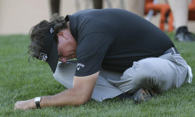 Phil Mickelson stretches on the grass as his playing partners finish the 16th hole during the second round of the Texas Open golf tournament on Friday, March 28, 2014, in San Antonio. (AP Photo/Eric Gay)