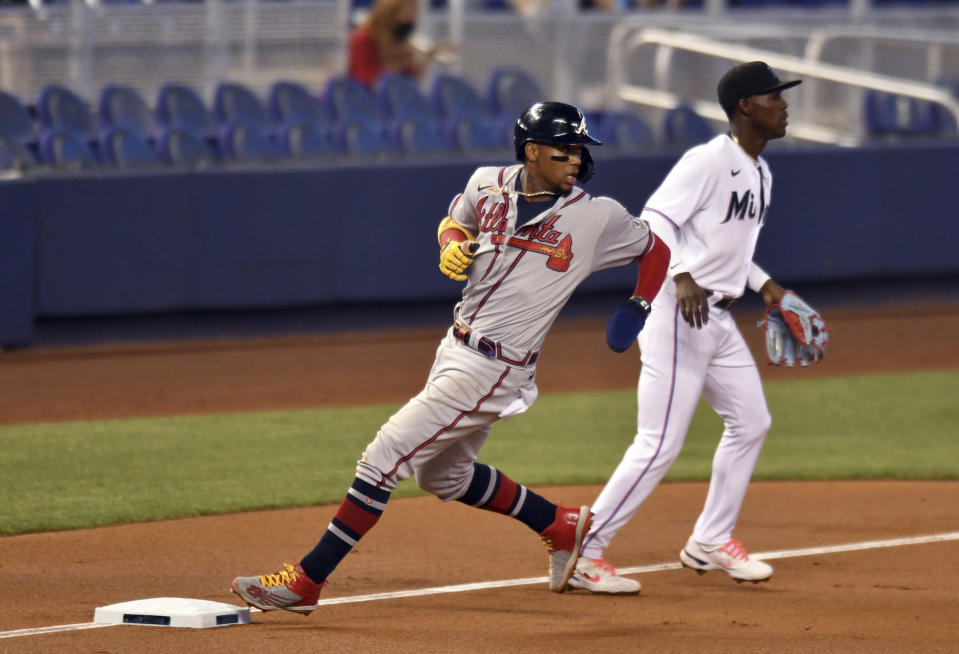 Atlanta Braves' Ronald Acuna Jr., left, advances third base as Miami Marlins' Jazz Chisholm Jr. looks on during the first inning of a baseball game, Sunday, June 13, 2021, in Miami. (AP Photo/Jim Rassol)