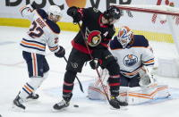 Ottawa Senators left wing Nick Paul tries to deflect the puck under pressure from Edmonton Oilers defenseman Tyson Barrie as goaltender Mikko Koskinen stays focused during the first period of an NHL hockey game Wednesday, April 7, 2021, in Ottawa, Ontario. (Adrian Wyld/The Canadian Press via AP)