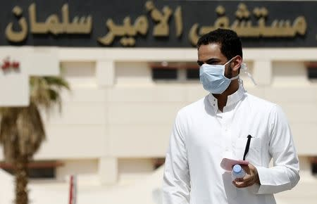 A man wearing a mask walks outside Prince Salman bin Abdulaziz hospital, in Riyadh in this June 6, 2014 file photograph. When Saudi Arabia announced last week that it had found 113 more cases of the deadly Middle East Respiratory Syndrome (MERS), it didn't just force a rethink of the threat the virus poses, it exposed dangerous institutional failings. REUTERS/Faisal Al Nasser/Files