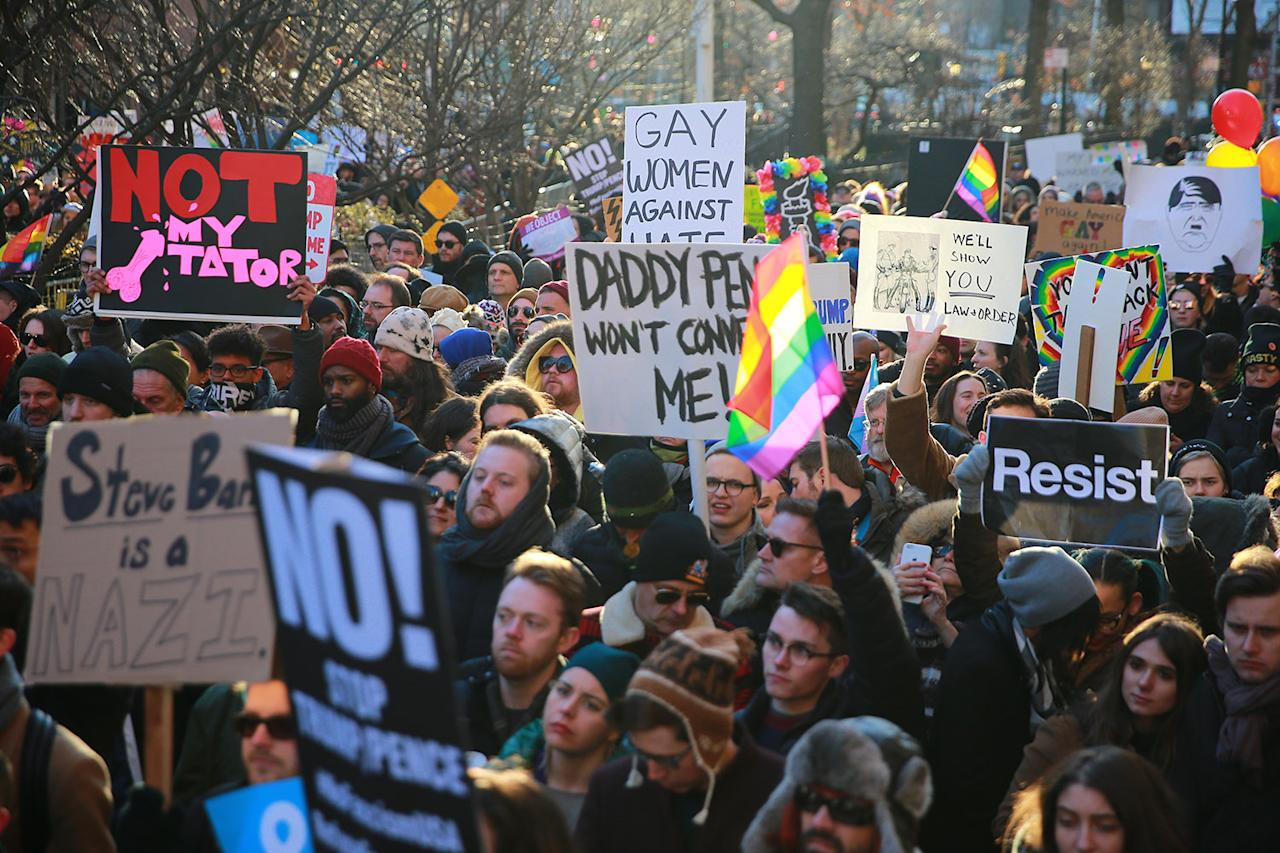 <p>People hold signs and flags at a rally in front of the Stonewall Inn in solidarity with immigrants, asylum seekers, refugees, and the LGBT community, Feb. 4, 2017 in New York. (Photo: Gordon Donovan/Yahoo News) </p>