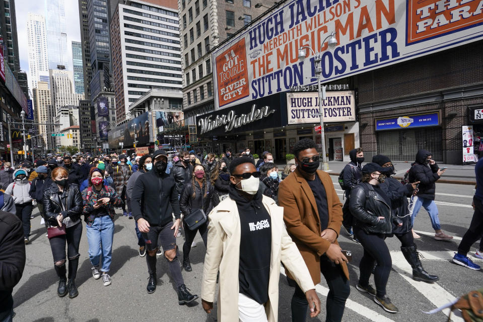 Protesters march past the Winter Garden Theatre in Times Square during a rally and march, Thursday, April 22, 2021, in New York. Hundreds of theater workers marched down Broadway on Thursday, rallying to demand more inclusion for minorities and the disabled, protesting producer Scott Rudin and to call for greater transparency from their union, Actors' Equity Association. (AP Photo/Mary Altaffer)