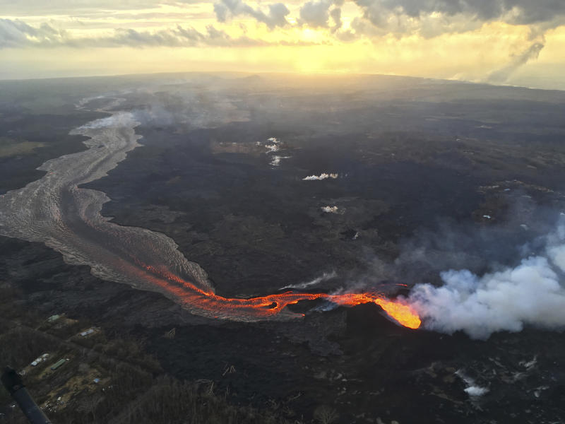 In this Tuesday, July 17, 2018 photo provided by the U.S. Geological Survey, sunrise is seen over the Kilauea volcano lower East Rift Zone in Hawaii. The small, rural town of Pahoa is the gateway to the eruption pouring rivers of lava out of Hawaii's Kilauea volcano. Tourism to parts of the island has plummeted since the volcano began erupting in a residential neighborhood and burning down homes in May. (U.S. Geological Survey via AP)