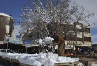 A vendor removes snow from his stall after heavy snowfall in Quetta, capital of Pakistan's southwestern Baluchistan province, Monday, Jan. 13, 2020. Severe winter weather has struck parts of Afghanistan and Pakistan with heavy snowfall, rains and flash floods that left more than 54 dead, officials said Monday as authorities struggled to clear and reopen highways and evacuate people to safer places. (AP Photo/Arshad Butt)