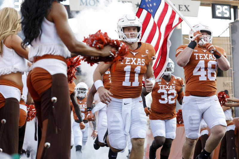 Texas Longhorns QB Sam Ehlinger and his brother Jake Ehlinger run onto the field before the game against the Louisiana Tech Bulldogs on Saturday. (Getty)