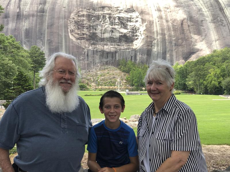 """Paula and Michael Smith pose for a photo with their 10-year-old grandson, Evan, in front of a giant carving of Confederate figures during a visit to Stone Mountain Park, Monday, June 29, 2020. """"The mountain itself is absolutely breathtakingly beautiful and the carving is an engineering marvel,"""" said Paula Smith, a 70-year-old white woman who dismissed talk of removing or altering the carving as an attempt to """"steal American history."""" (AP Photo/Kate Brumback)"""
