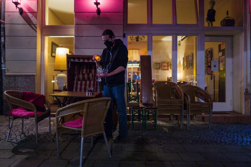 A bar owner closes up at a bar in Berlin's Prenzlauer Berg district on October 10, 2020. - Stolz, along with other bar owners in Berlin, has challenged local authorities over the re-introduction of a curfew for bars in the capital, which are, from October 10 onwards, forbidden to operate between 11 PM and 6 AM. (Photo by JOHN MACDOUGALL / AFP) (Photo by JOHN MACDOUGALL/AFP via Getty Images)
