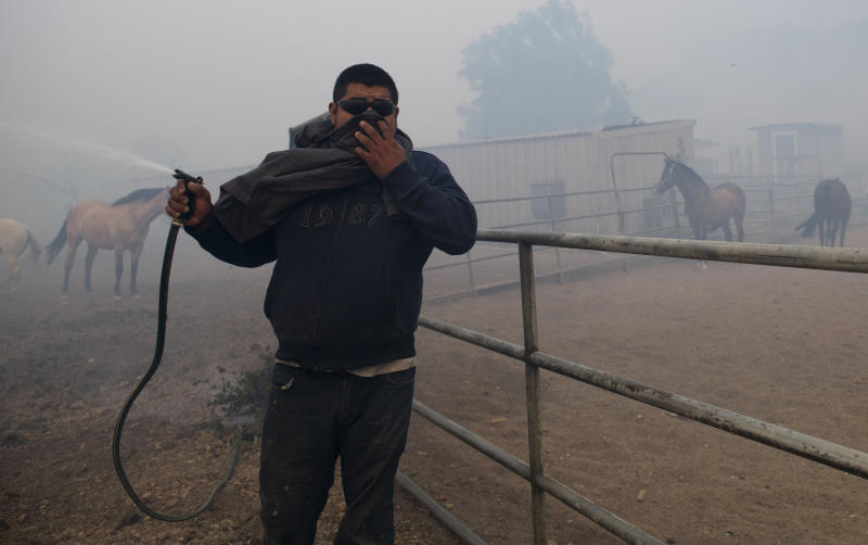Alejandro Garrido sprays a water hose at a horse ranch as smoke from wildfires burning in the region fills the air in Simi Valley, Calif., Oct. 30, 2019. A brush fire broke out just before dawn in the Simi Valley area north of Los Angeles. (Photo: Christian Monterrosa/AP)