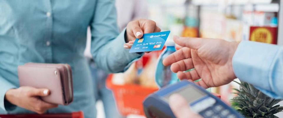 Woman at checkout in supermarket, she pays using credit card, shopping and retail concept