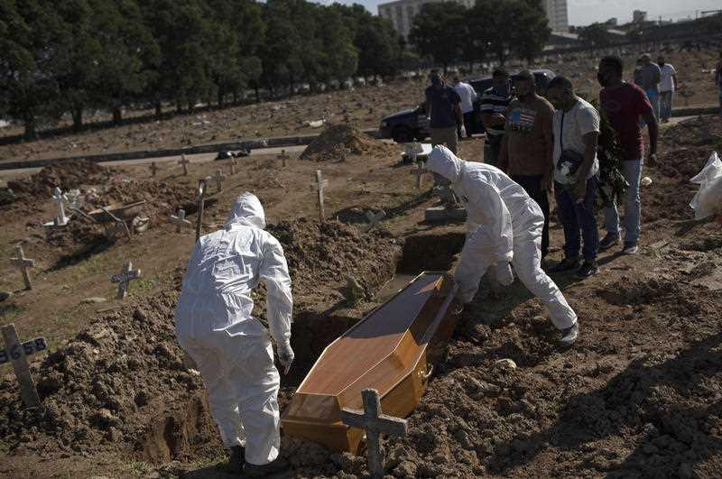 Cemetery workers in protective gear place the casket of 22-year-old COVID-19 victim Amanda da Silva into her grave site at the Caju cemetery in Rio de Janeiro, Brazil.